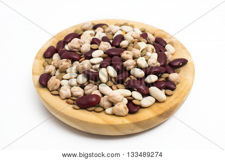 Legumes in wooden plate on white background.