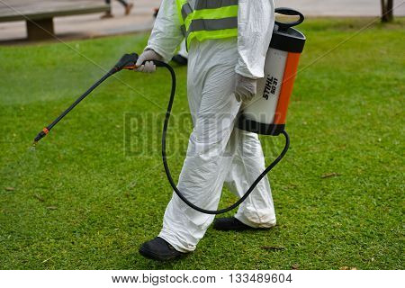 Buenos Aires Argentina - March 3 2016: Employee of the Ministry of Environment and Public Space fumigates for Aedes aegypti mosquitos to prevent the spread of Zika virus and dengue fever in park.