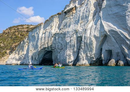MELOS GREECE - SEPTEMBER 4 2012: People with kayaks exploring the caves next to Gerontas beach off the south coast of Melos island.