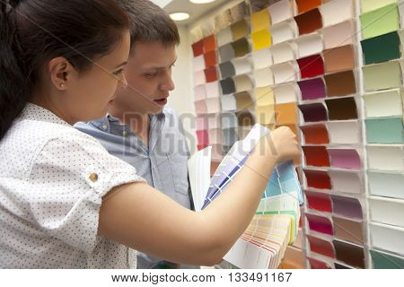 Couple select paint color and look matching samples at household store