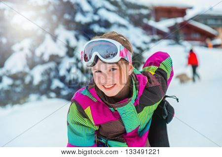 Happy kid in ski outfit and goggles at the ski resort