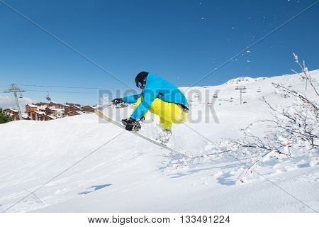 Young man jumping with snowboard in winter mountains