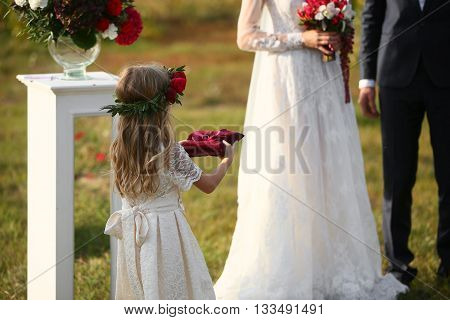 little girl Carrying Wedding Ring On Cushion.