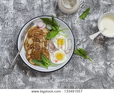 Savory whole grain pancakes boiled egg and fresh spinach and radishes on the enamel plate on the stone texture. Healthy breakfast or snack