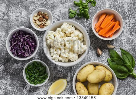 Variety of fresh vegetables in bowls - potatoes red and cauliflower spinach green onions carrots nuts olive oil cilantro. Raw ingredients. Vegan table. Top view