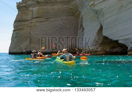 MELOS GREECE - SEPTEMBER 4 2012: People with kayaks exploring the rock formations and caves at Kleftiko at the southwest coastline of Melos island.