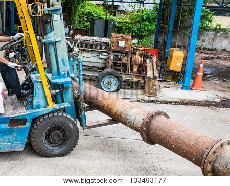 Forklift Moving big Steel Pipe with Old diesel generator background