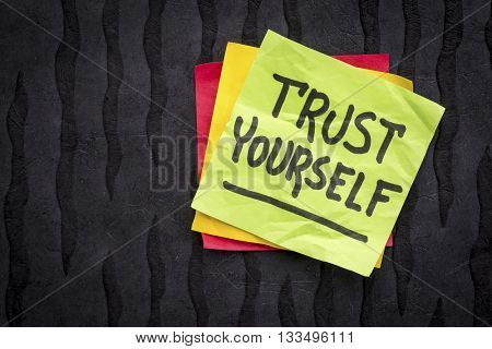 trust yourself reminder note - handwriting on a sticky note against black Nepalese lokta paper