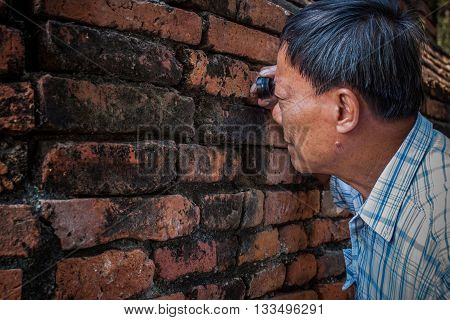 old Archaeologist using magnifying lens watching on ancient old brick wall in working site