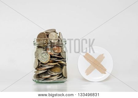 Coins in glass jar, and covered with cross symbol