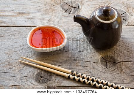 Chopsticks on wooden table with chili sauce