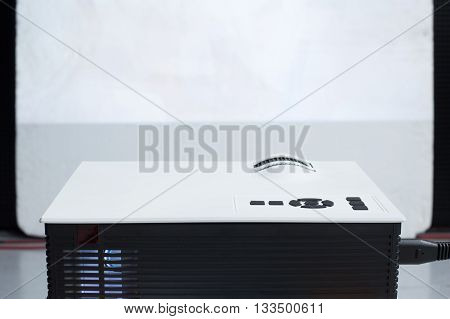 Closeup of projector for presentation with blank screen in front
