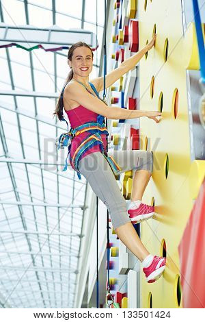 Young smiling woman in safety harness is practicing rock-climbing on the climbing wall in gym
