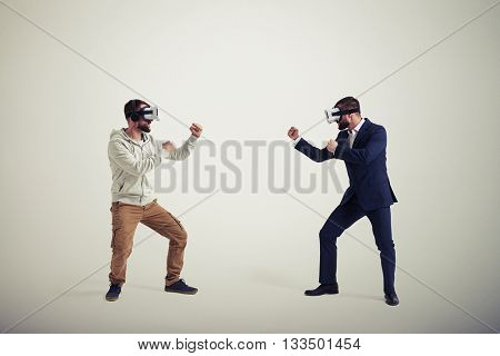 Two men, one in casual clothes, another in dark business suit, are wearing virtual reality glasses and standing in fighting poses ready to start their combat in virtual reality