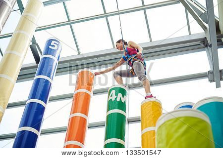 Young sportswoman in safety equipment is exercising on the indoor sport venue with columns of different height, she is standing on a column ready to make a step on the next and higher one