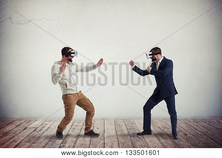Two men, one in casual clothes, another in dark business suit, are wearing virtual reality glasses and combating in virtual reality in white room with wooden floor