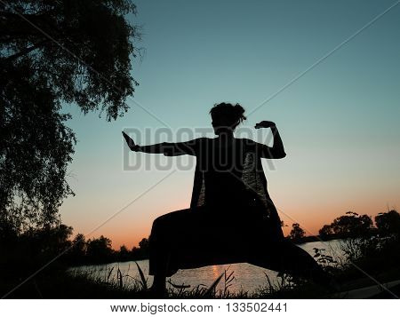 Kung fu woman in harem pants on sunset sky background