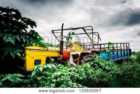 Abandoned vintage yellow tractor with blue trailer in Nepal