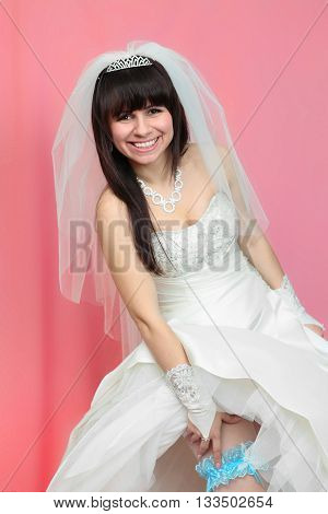 beautiful bride with a blue garter on the pink background