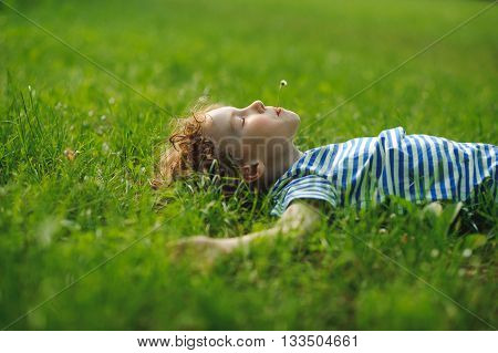 The boy of 8-9 years lies on a back in a dense green grass. He has stretched hands in the parties and has closed eyes. In a mouth at the child a small floret.