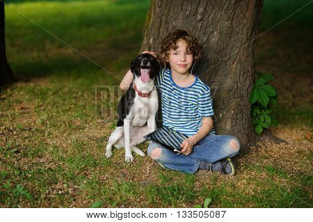 The boy with a dog sits on the earth under a tree. The child sits having crossed legs. He has put a hand on the head of a pet. On a lap the boy has a tablet. On a face a thoughtful smile.