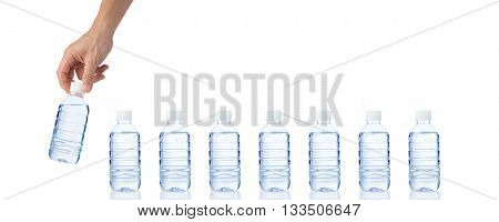 Male's hand grabs and holds a bottle of water with seven more bottles of water on white table isolated white background with copyspace