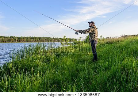 bearded man in a blue baseball cap on the river throws a spinning fishing