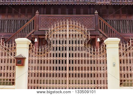 Front gate with antique blockhouse background .