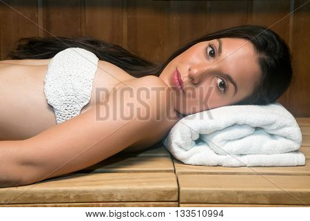 Young Woman In Towel Relaxing On Bench In Sauna