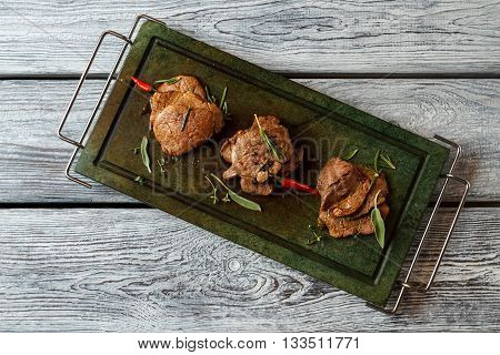 Green tray with cooked meat. Chili pepper and brown meat. Taste the delicacy. Veal medallions on stone tray.