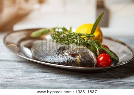 Raw fish with herbs. Plate with raw fish. Dorado fish and lemon. Simple recipe of seafood dish.