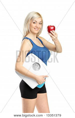 Happy Athlete Holding A Weight Scale And Red Apple