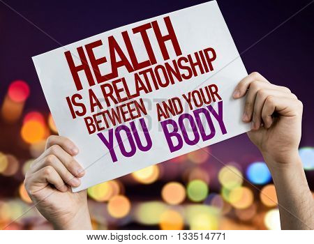 Health is a Relationship Between You and Your Body placard with night lights on background