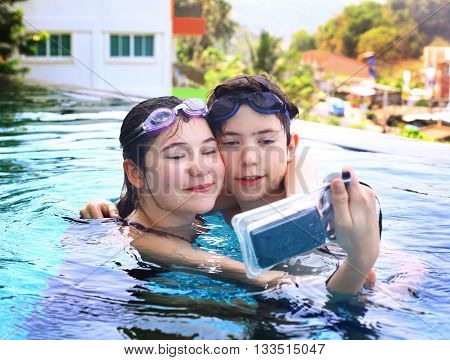 teen siblings brother and sister take photos with underwater cover camera close up portrait in open air thai swimming pool
