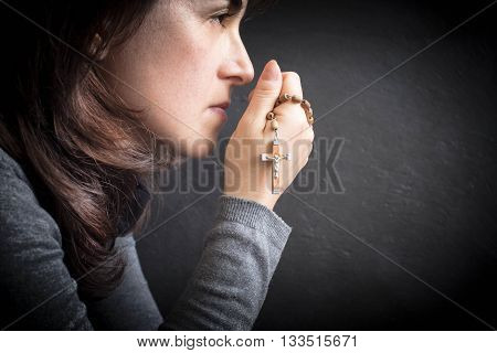 woman believer with rosary over dark background