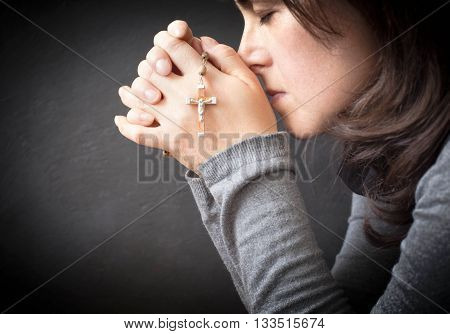 Woman Meditatin With Rosary Over Dark Background