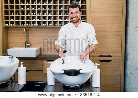 Portrait of handsome smiling hairdresser with water tap near sink at salon barbershop.
