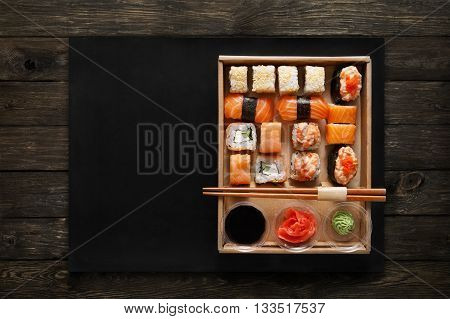 Japanese food restaurant, sushi maki gunkan roll plate or platter set. Chopsticks, ginger, soy sauce, wasabi. Sushi on rustic wood background and black mat, take away, delivery box. Top view.