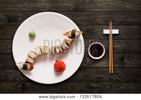 Japanese food restaurant, unagi sushi maki gunkan roll plate or platter set. Set with chopsticks, ginger, soy, wasabi. Sushi with eel at rustic wood background. Top view, flat lay.