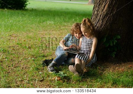 Boy with girl of 7-8 years sit under an old tree and excitedly look at the laptop screen. Children are very keen. They with inreresy look at the screen..