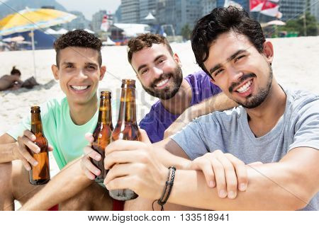 Three guys drinking beer at beach outside at beach in the summer