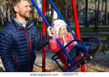 Father Riding Little Daughter on Seesaw in Autumnal Park Bearded Casual Clothing Man Outdoor Sunny Day Autumnal Background