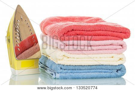 Steam iron and ironed colored towels isolated on white background.