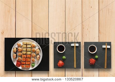 Japanese food restaurant, sushi maki gunkan roll plate or platter set. Set with chopsticks, ginger, soy, wasabi. Sushi at black stone and wooden planks background. Top view, flat lay, copyspace