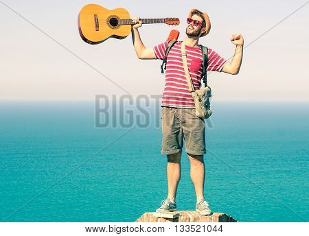 Man reaching the top exulting with arms raised up on blue ocean background - Cheering traveler guy standing at summit of hill - Casual style concept of climb to success and achievement of life goals