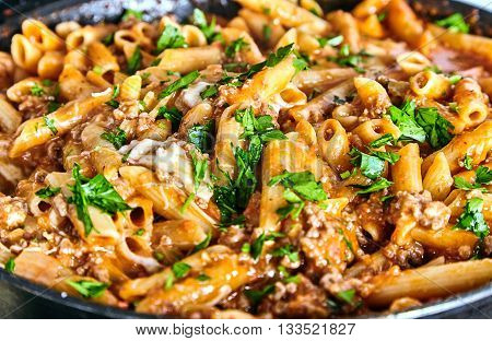 Close up of american chop suey - pasta dish with beef, tomato sauce, mozarella cheese, spices and parsley. Italian-American cuisine