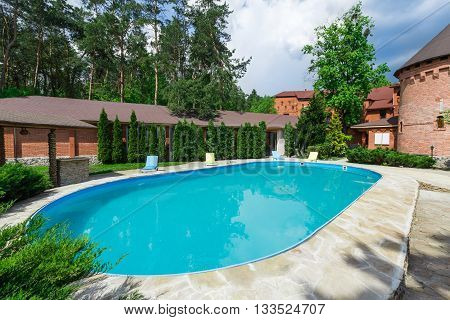 Country resort. Luxury swimming pool beside the hotel in medieval british castle style. Landscape design of resort territory. Swimming pool outdoors. Blue water in summer park.