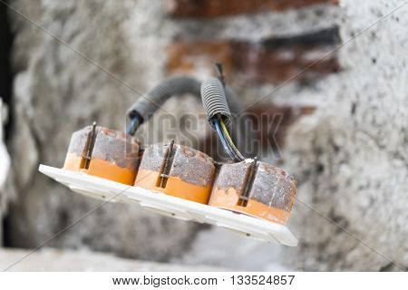 Close Up Still Life of Power Outlet - Plug with Exposed Wires Connected to Wall in Background with Concrete and Exposed Brick - Power and Home Renovation Building Concept