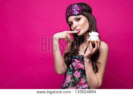 Funny young woman in sleeping mask and pajamas, sweets in the hands on a pink background. The beauty of the face. Photos shot in studio