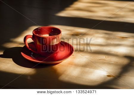 Profile Still Life of Red Cup of Coffee with Saucer on Wooden Kitchen Table with Bright Sunlight Streaming Through Window with Shadows and Ample Copy Space